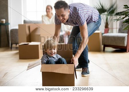 Father Helping Cute Little Son Riding In Box, Happy Dad Playing With Small Boy After Relocation, You
