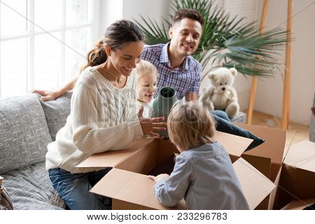 Happy family with two kids unpacking boxes after relocation moving into or settling in new home concept, excited small children helping parents with belongings sitting on sofa in living room together poster