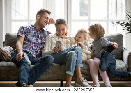 Cheerful Young Family With Kids Laughing Watching Funny Video On Smartphone Sitting On Couch Togethe