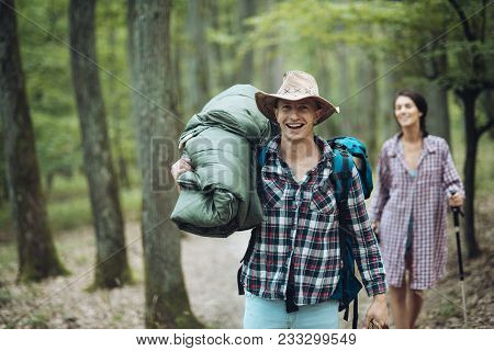 Young Couple With Happy Faces Walks. Man With Woman Hiking With Overnight Stay Or Picnic. Couple In