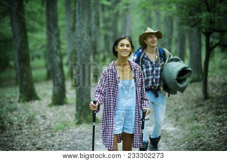 Young Couple With Happy Faces Walks. Tourists Concept. Couple In Love Hiking In Forest With Touristi