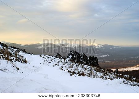 Winter Mountain Landscape Of The North Urals During The Dawn With Rocks In The Foreground And Sunlit