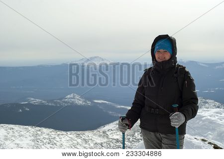 Traveler Woman With Poles For A Nordic Walking Or Ski Poles In Hands Against A Background Of A Winte