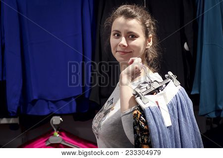 Young Girl Buys Clothes In Fashionable Boutique Shop. Shopping Concept. The Girl In The Clothing Sto