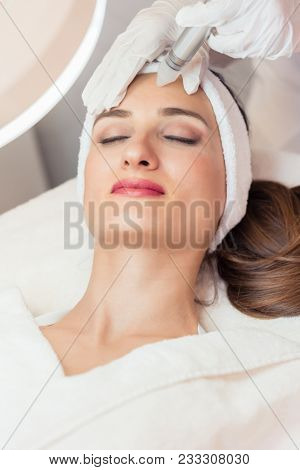 Close-up of the face of a beautiful woman smiling during innovative facial treatment for rejuvenation in a beauty center with modern technology
