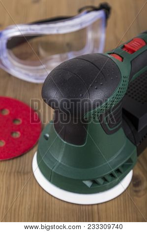 Orbital power sander with red sanding disc on a wooden workbench poster