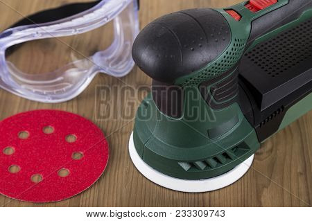 Orbital Power Sander With Safety Goggles And Sanding Disc On A Wooden Workbench