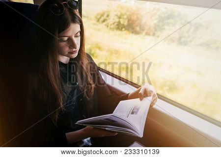 Stylish Hipster Girl Reading Book At Window Light In Train. Travelling By Train Concept. Beautiful Y
