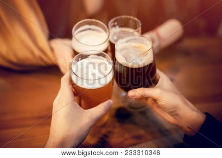 Friends Clinking And Toasting With Delicious Craft Beer In Bar. Group Of People Cheering And Enjoyin