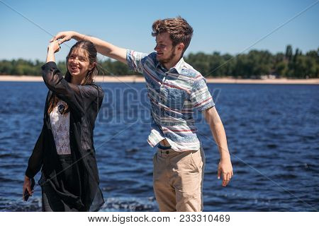 Stylish Hipster Couple Dancing At Windy River In Summer City. Happy Man Having Fun With His Beautifu