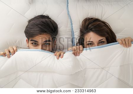 Top View Of A Couple In Love Lying In Bed, Hiding And Peeking Under The Sheets