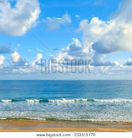 Clear sunny day at seaside. Yellow sand and blue ocean against background of sky.