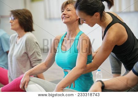 Group of senior people in fitness room exercising with coach