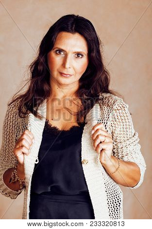 Mature Brunette Real Middle Age Woman Well Dressed Posing Smiling On Warm Brown Background, Aging Co