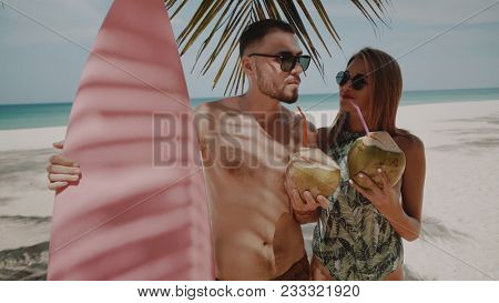 Young happy couple in swimwear with pink surfboard drinking coconut milk, enjoying sunny summer day on their beach tropical holiday