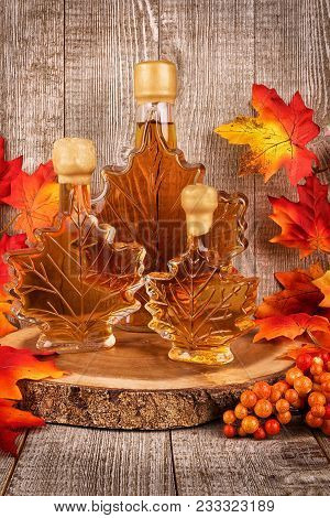 Maple Syrup Bottles On A Wooden Plank. Maple Leaves In Decoration.