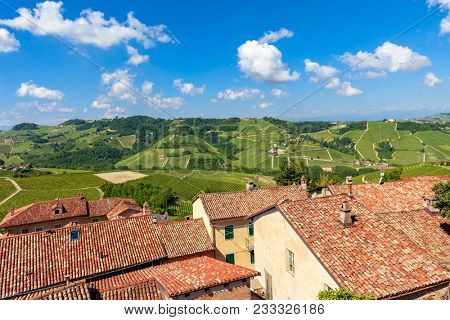 View of rural houses with red roofs overlooking green vineyards on the hills under blue sky with white clouds in spring in Piedmont, Northern Italy.