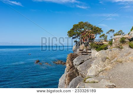 Villa on the cliff overlooking beautiful Mediterranean sea under blue sky in small town of Recco in Liguria, Italy.