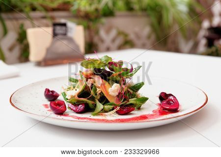 Light salad with goat cheese and cherry dressing, toned image