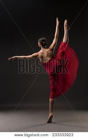 Beautiful Girl In Red Chiffon Dress Dancing Gracefully In Dark Room Rearview