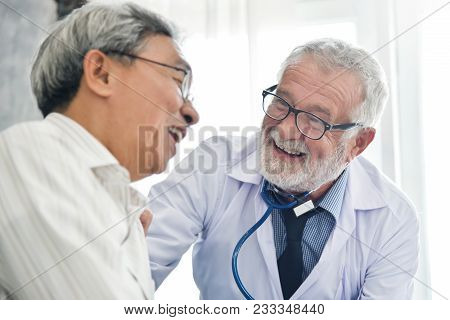 Happiness People.  Senior Male Doctor And Asian Male Patient Are Talking In The Medical Room Togethe