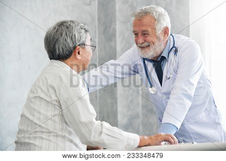 Senior Male Doctor Is Comforting Asian Male Patient In Medical Room.