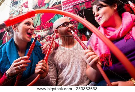 Women and man enjoying recreational shisha in hookah lounge on the weekend