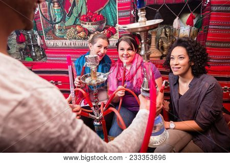 Group on women and men being served a hookah in shisha cafe, they are good friends