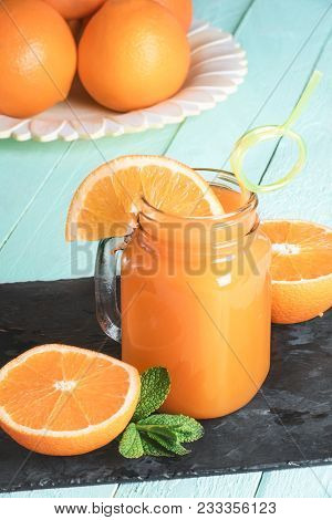 Mason Jar Full Of Fresh Orange Juice, With A Funny Straw, Surrounded By Sliced Oranges And Mint Leav