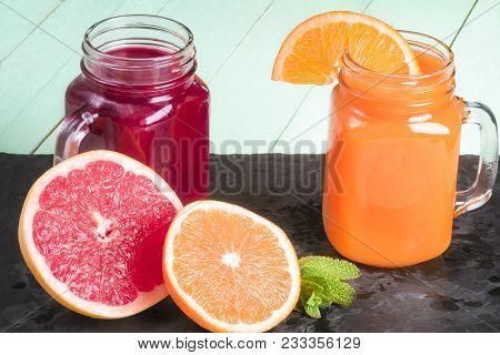 Freshly Squeezed Orange Juice And Grapefruit Nectar, In Mason Jars, On A Black Stone Plateau, With S