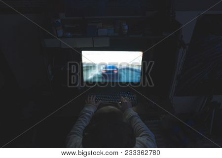 A Man Plays Games At Night On A Computer. Gamer Plays Races At Home. The Hands On The Keyboard Contr