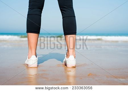 Close Up Of A Female Jogger Standing On The Beach