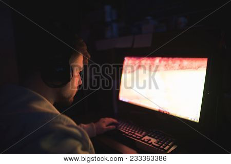 Gamer Plays Computer Games In A Dark Room. A Man In The Headphones Plays Computer Games At Night. Ga