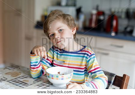 Adorable Happy Little Blond Kid Boy Eating Homemade Cereals For Breakfast Or Lunch. Healthy Eating F