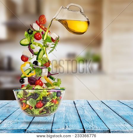 Flying vegetable greek salad with pouring olive oil from saucer. Blur kitchen on background. Healthy eating and lifestyle. Very high resolution image