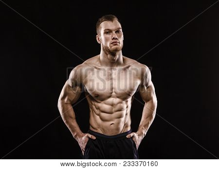 Aggressive Man Is A Fighter, A Bodybuilder With A Naked Torso On A Black Background. Strength And Be