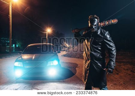 Maniac with bloody baseball bat against black car