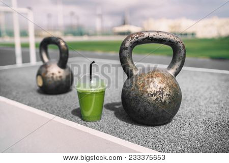 Green smoothie detox at gym with kettlebell weights.