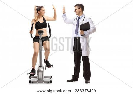 Young woman exercising on a stationary bike and high-fiving a doctor isolated on white background