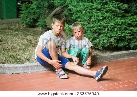 Two Boy Brothers Single-breasted Homeless Homeless Sit On The Curb In The Late Evening.