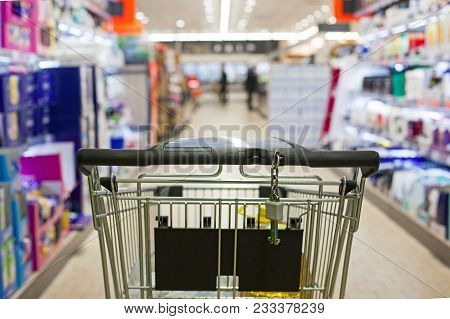 Shopping Cart Full Of Grocery On Blurred Supermarket Aisle.