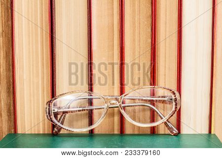 Glasses And Many Hardback Books On Wooden Shelf. Education Background. Library Concept