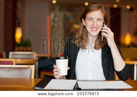 Portrait Of Cheerful Young Caucasian Female Freelancer Drinking Coffee, Talking On Mobile Phone, Loo