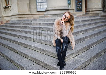 Blonde Girl At Fur Coat And Glasses Sitting On Stairs.