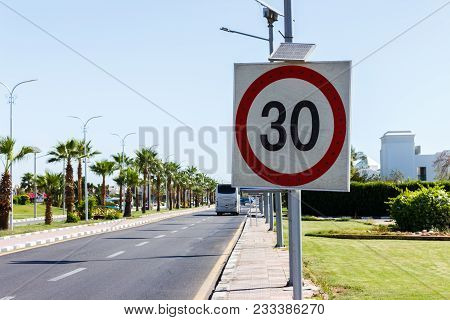 Speed Limit Sign With Solar Panel In The Road With Palm Tree On A Summer Day. The Speed Limit Is 30