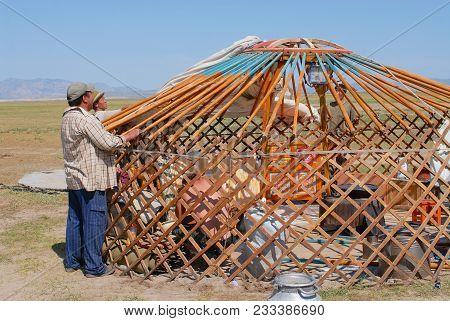 Kharkhorin, Mongolia - August 25, 2006: Unidentified Mongolian Men Assemble Yurt (nomadic Tent) In S