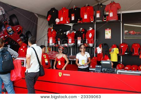 SEPANG, MALAYSIA - APRIL 8: Unidentified salesgirls from the Ferrari merchandise shop wait for customers at the circuit grounds of the Petronas Malaysian F1 Grand Prix on April 8, 2011 in Sepang, Malaysia.