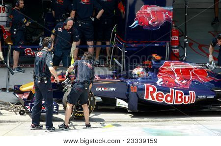 SEPANG, MALAYSIA - APRIL 8: Scuderia Toro Rosso pit crew works on Sebastien Buemi's car during pit-stop on the practice day of the Petronas Malaysian F1 Grand Prix on April 8, 2011 Sepang, Malaysia.