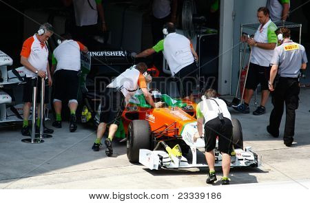 SEPANG, MALAYSIA - APRIL 8: Force India F1 Team pit crew pushes Adrian Sutil back into the pits on the first practice day of the Petronas Malaysian F1 Grand Prix on April 8, 2011 Sepang, Malaysia.