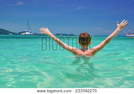 Happy Boy With Arms Raised Rejoices Sea. Vacation Concept On Tropical Sea With Turquoise Water. Seas